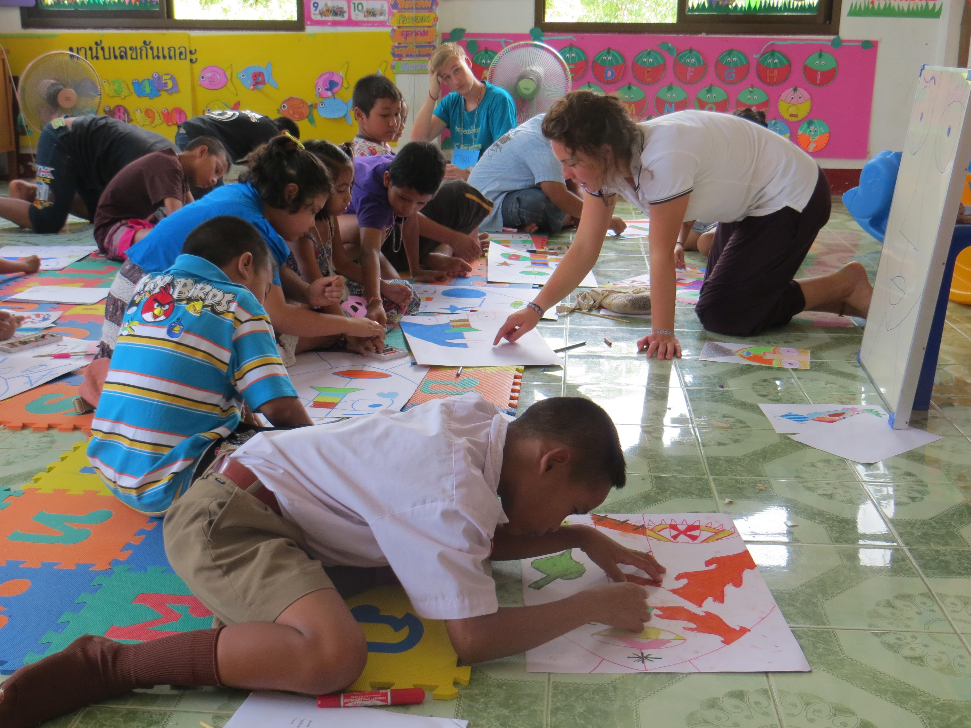 Students complete an art projects with a volunteer teaching English in Thailand.